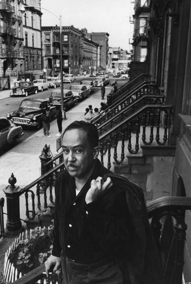 African American poet/writer Langston Hughes standing on the stoop in front of his house in Harlem.